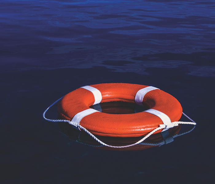 Orange and white Life ring floating in the water.
